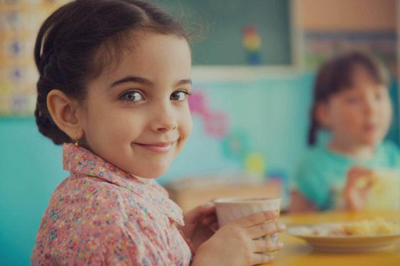 Petite fille souriante buvant un chocolat chaud