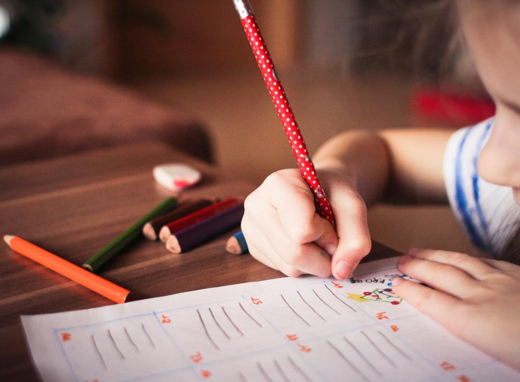 Enfant écrivant au crayon de couleur
