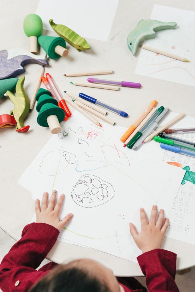 Enfant faisant du dessin avec des jouets sur la table