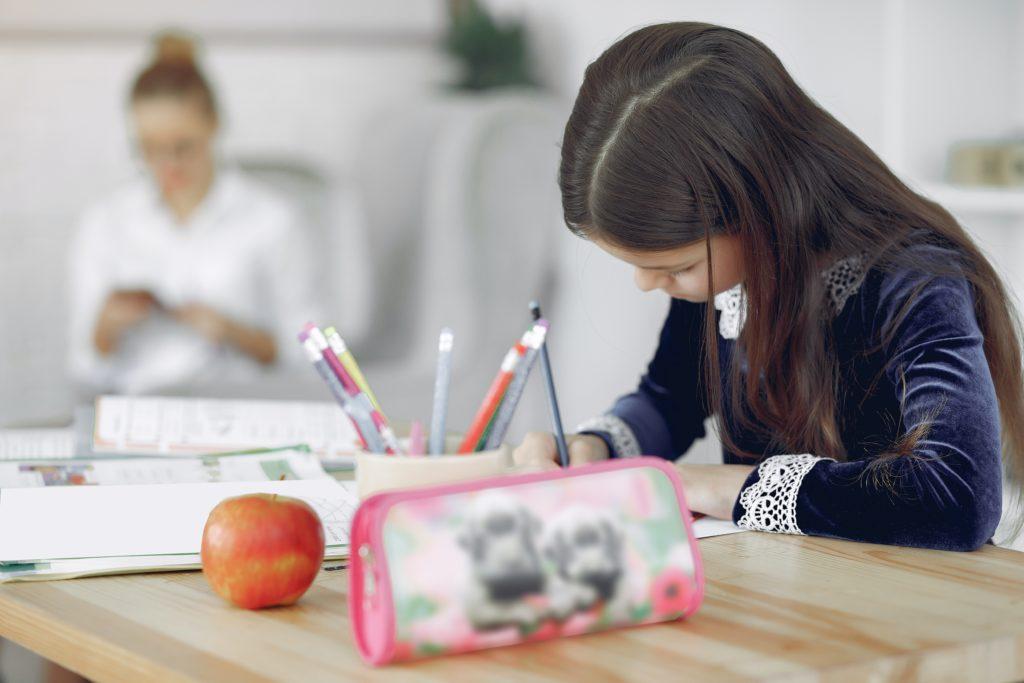 Jeune fille fait ces devoir a un bureau sous la supervision d'un adulte